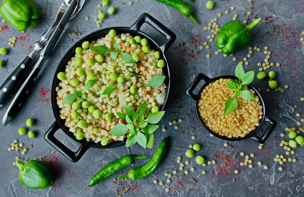 ptitim israelischer couscous mit gemüse und grünen erbsen - griechischer couscous salat stock-fotos und bilder