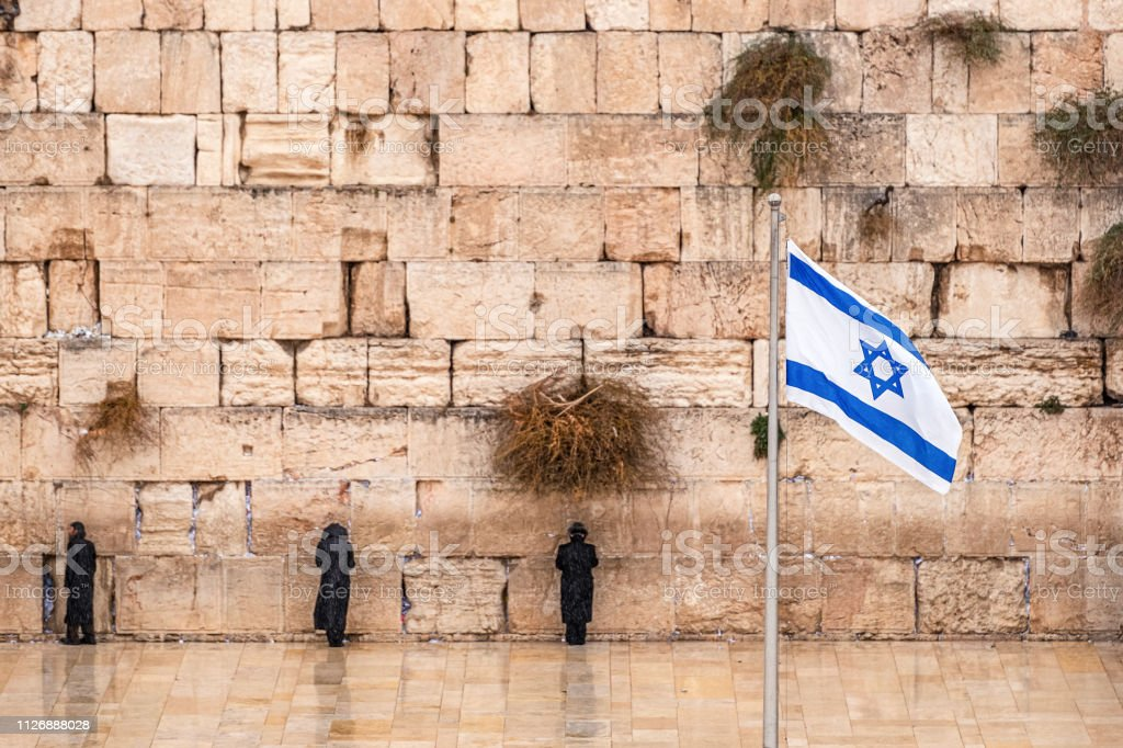 Israeli flag against the western wall  on a cloudy day Israeli flag against the western wall  on a cloudy day Ancient Stock Photo