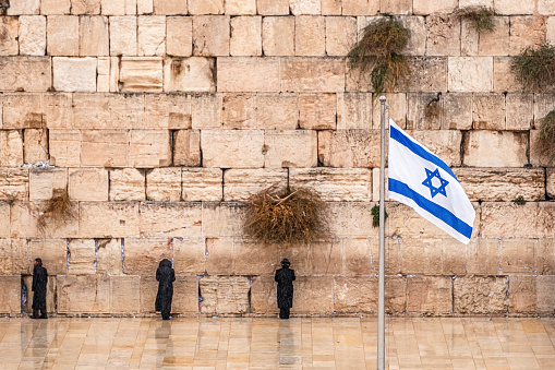 Israeli Flag Against The Western Wall On A Cloudy Day Stock Photo - Download Image Now