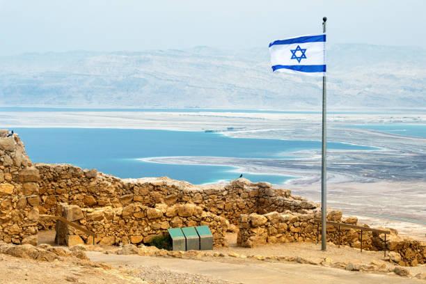 bandeira de israel com as ruínas em massada com mar morto no fundo - israel - fotografias e filmes do acervo