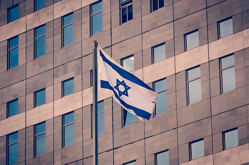 istock Israeli National flag waving on the background of the government building. 1165097002