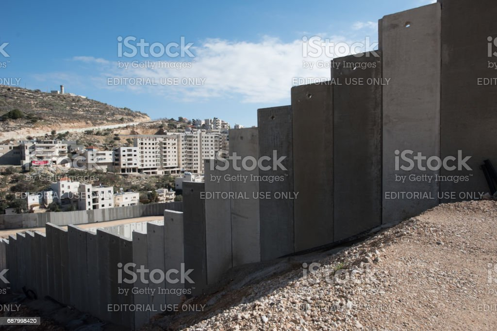 Israeli separation wall and Palestinian buildings in West Bank stock photo