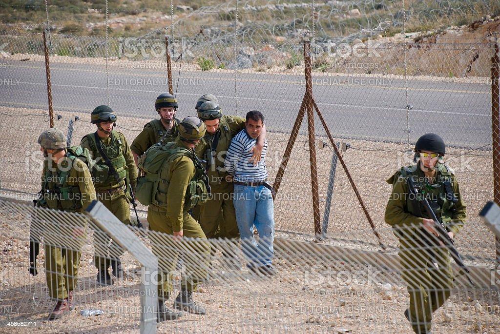 Israeli soldiers arresting a Palestinian man in Bil'in royalty-free stock photo
