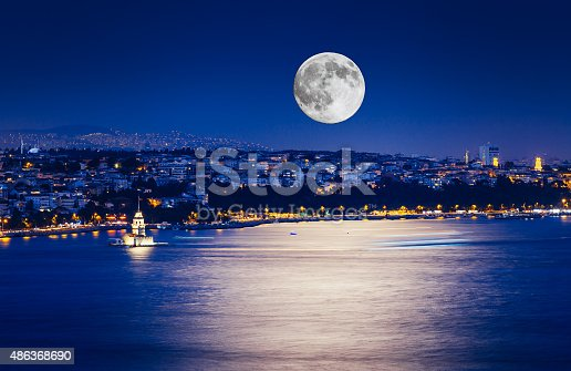 The Maiden's Tower with fullmoon and lights on sea in Istanbul, Turkey