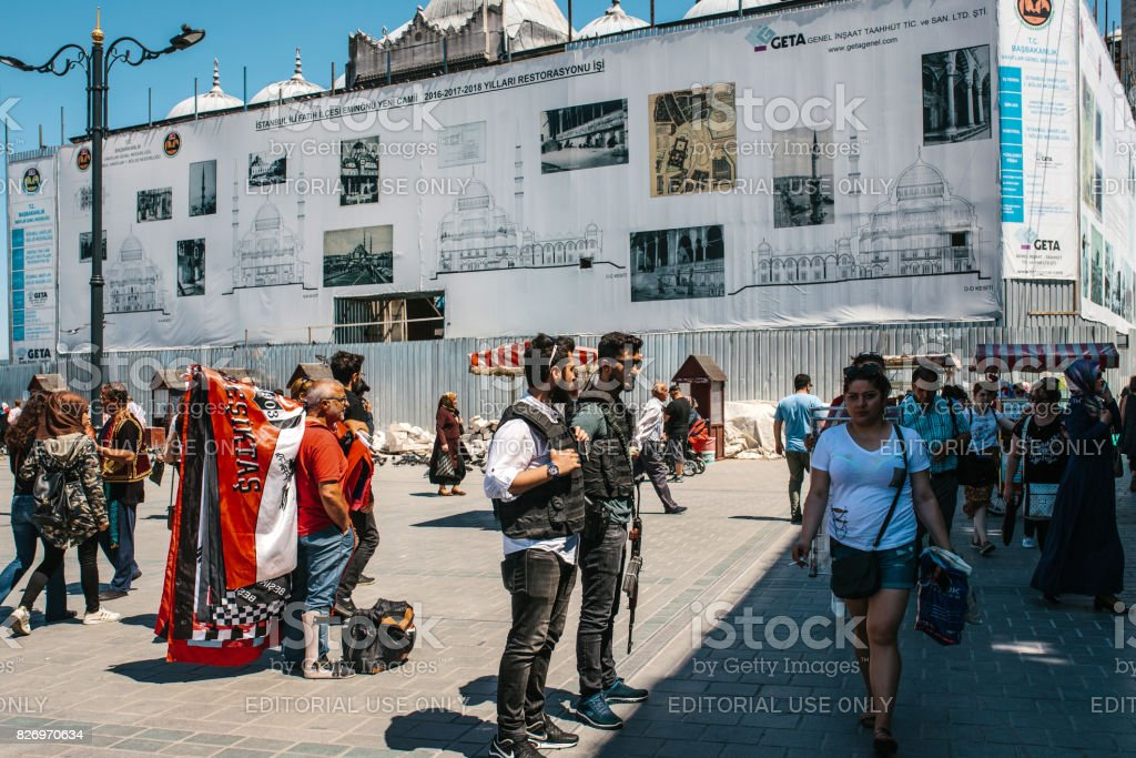 Istanbul, June 15 2017: People at Eminonu Square in the middle of the day - police officers, man with medical cast on his leg, casually dressed woman in white t-shirt and random passerby. stock photo