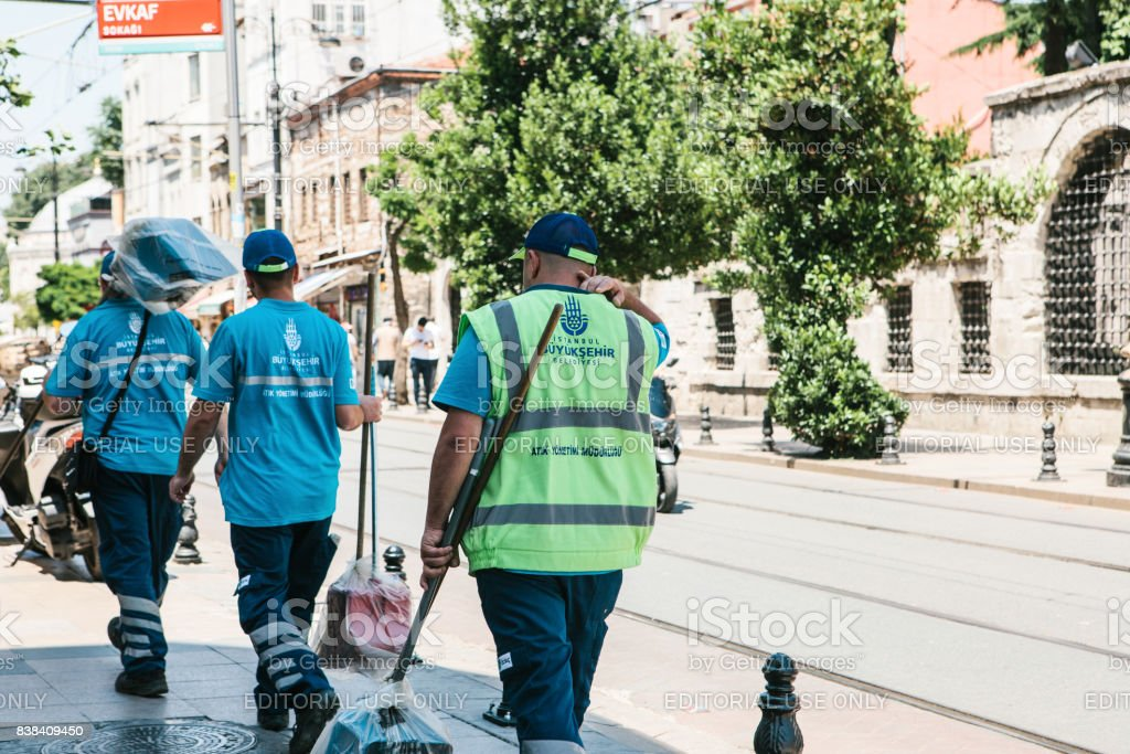 Istanbul, June 15, 2017: Three street janitors in uniforms are walking down the street holding brooms and dust pans. stock photo