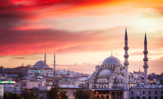 Istanbul skyline at sunset with dramatic sky, featuring two mosques in the foreground.