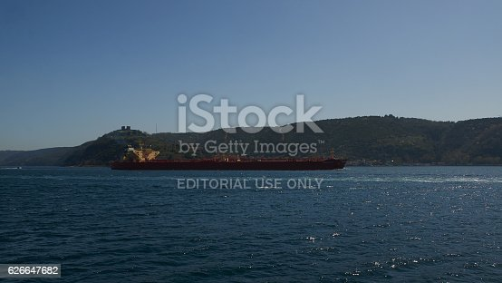 Istanbul, Turkey - April, 05, 2016, Cargo ship on background of Asian side of Bosporus, slice of life, Sunny spring day, perfect weather, beginning of tourist season, editorial.