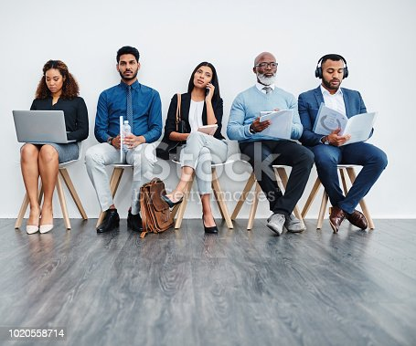 Studio shot of a group of diverse businesspeople waiting in line