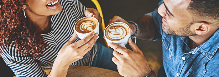 Cropped shot of a happy young couple sitting together in a cafe and enjoy a coffee during a date