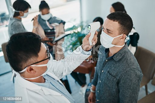 Shot of a young man getting his temperature taken with an infrared thermometer by a healthcare worker during an outbreak