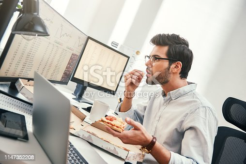 It can not be truth! Disappointed young trader is looking at monitor screen with trading charts and financial data while eating hot pizza in his modern office. Food concept. Business concept. Trade concept. Bad news