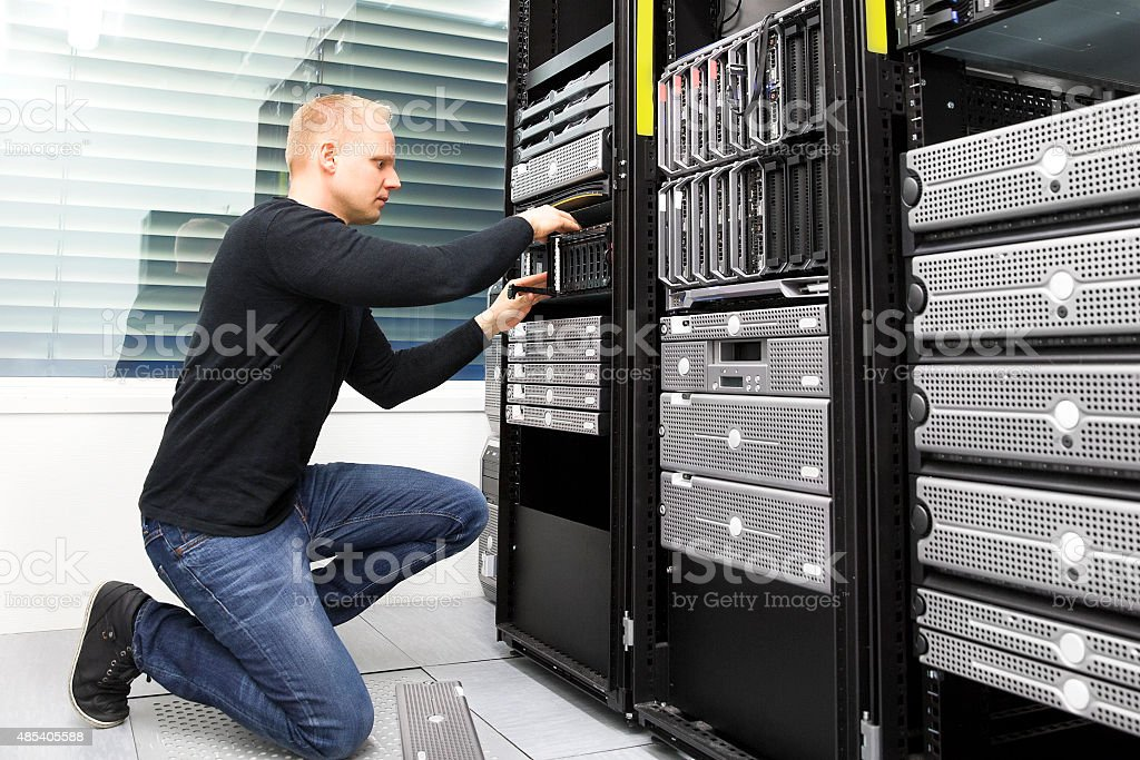 It consultant replaces harddrive in datacenter storage stock photo