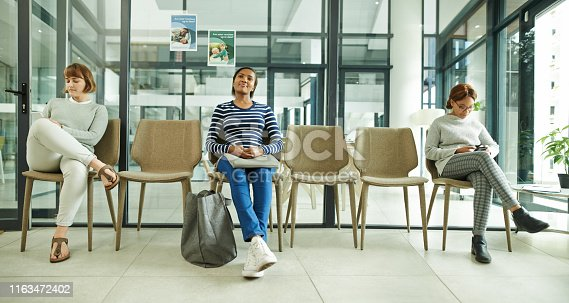 Shot of a group of young women sitting in the waiting room of a clinic