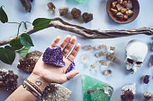 Closeup of an unrecognizable person holding a crystal with two hands over a table filled with more crystals inside during the day