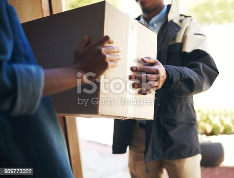 Shot of an unrecognizable woman receiving a package from a deliveryman at home during the day