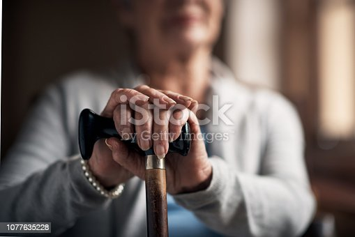 Shot of a senior woman sitting with a wooden cane