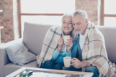 istock It is almost winter, so cold outside, but so sweet time we spend together! Happy cheerful peaceful couple of pensioners are resting,  relaxing, hugging, drinking tea with closed eyes at the weekend 926661360