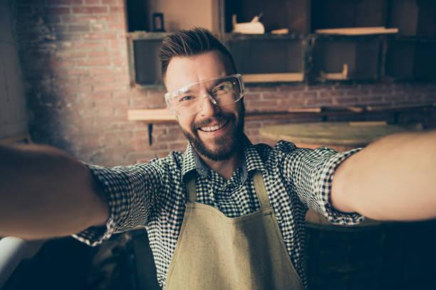 es ist live-übertragung! close-up-porträt von glücklich fröhlich fröhlich mit toothy lächeln begeistert bärtigen tragen schutzbrille zimmermann, er nimmt an seinem arbeitsplatz selfie - do it yourself videos stock-fotos und bilder