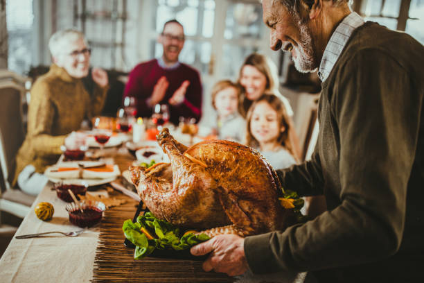 It is time for Thanksgiving turkey! Happy senior man bringing Thanksgiving turkey to the table for his family's lunch. dinner stock pictures, royalty-free photos & images