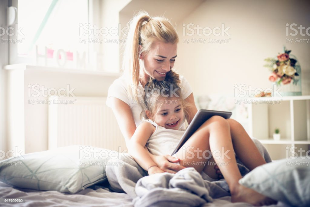 It is time to watch cartoon with mommy. Little girl. stock photo