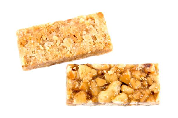 het is twee close-up van caramel pinda's bar geïsoleerd op een witte achtergrond. honing brosse pinda's geïsoleerd - kauwgomachtig stockfoto's en -beelden