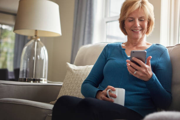 it just gets easier and easier to stay in touch - older woman phone stock photos and pictures