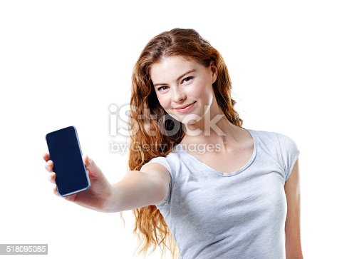Studio portrait of an attractive young woman holding out her mobile phone