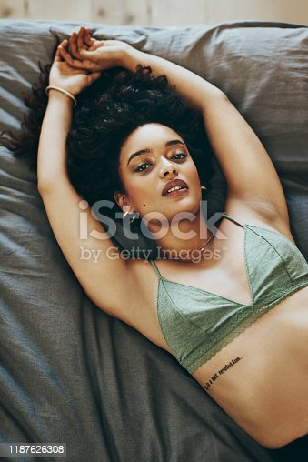 Shot of a beautiful young woman wearing underwear while relaxing in her bedroom