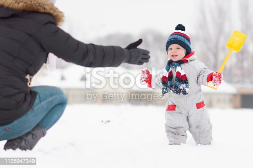 a little cute boy walking towards his mother who is waiting for her to come to her arms. Winter games in the snow of a mother and a little child. Little boy makes his first steps in the snow.