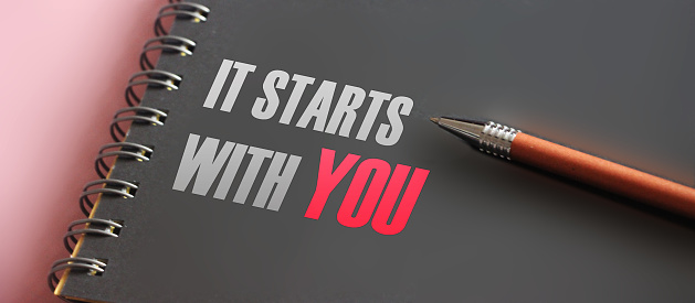 It Starts With You words printed in notebook and luxury pen. Self Motivation concept