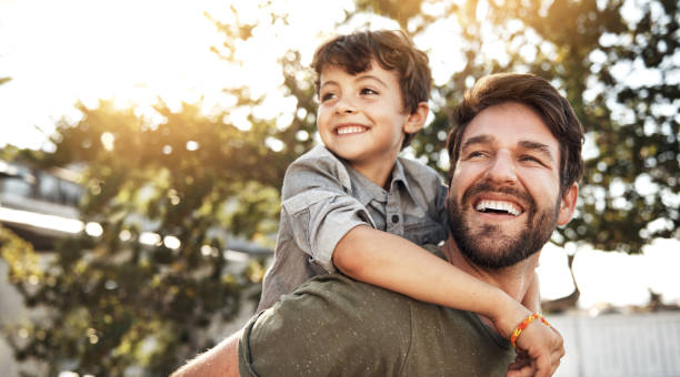 It takes a special person to be a dad Portrait of a happy father giving his little boy a piggyback ride in their backyard piggyback stock pictures, royalty-free photos & images