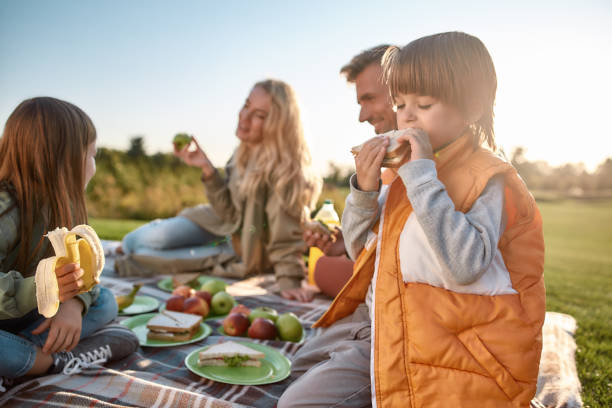 It tastes good. Happy family spending time in the park on a sunny day Portrait of little boy eating sandwich. Young parents having picnic with their children on blanket in park. Family and kids, nature concept. Horizontal shot picnic stock pictures, royalty-free photos & images