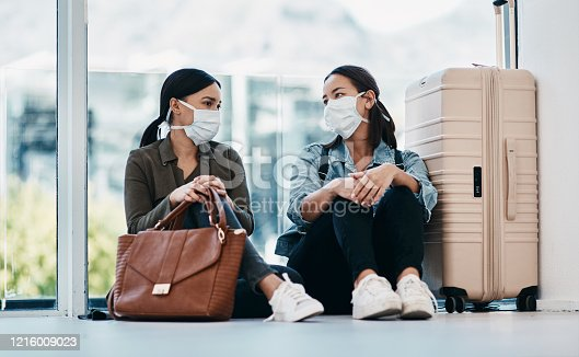Shot of two young women wearing masks while waiting together in an airport