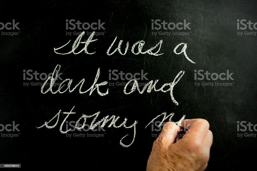 It was a dark and stormy night  written on  blackboard. stock photo