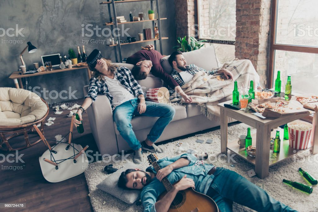 It was great party! Bearded, exhausted, tired, drunk guys are sleeping after night events on the floor and sofa in different pose in living room, having a lot of litter, garbage, rubbish around them - fotografia de stock