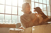 Shot of a young woman relaxing on the sofa at home with her dog