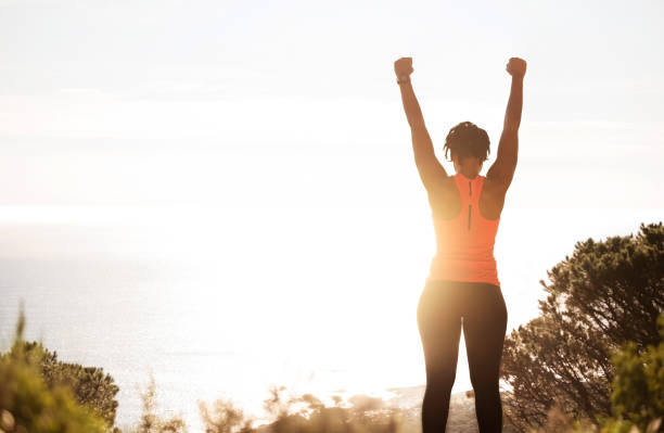 It was worth the climb Rear view of young active woman in sportswear with raised up hands enjoying beautiful sunshine while taking break after workout outside achievement stock pictures, royalty-free photos & images