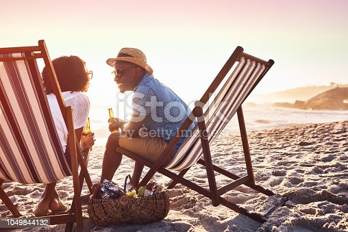 Shot of a happy young couple relaxing on chairs and having drinks at sunset on the beach