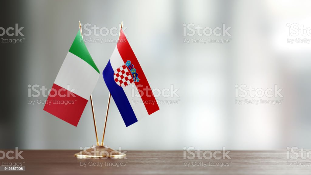 Italian And Croatian Flag Pair On A Desk Over Defocused Background - foto stock