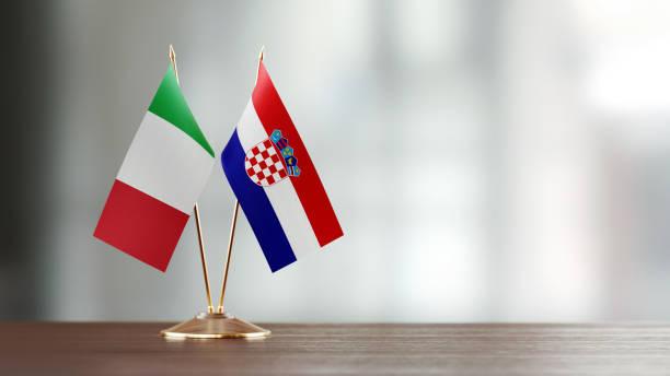 Par de bandeira italiana e croata em uma mesa sobre fundo desfocado - foto de acervo