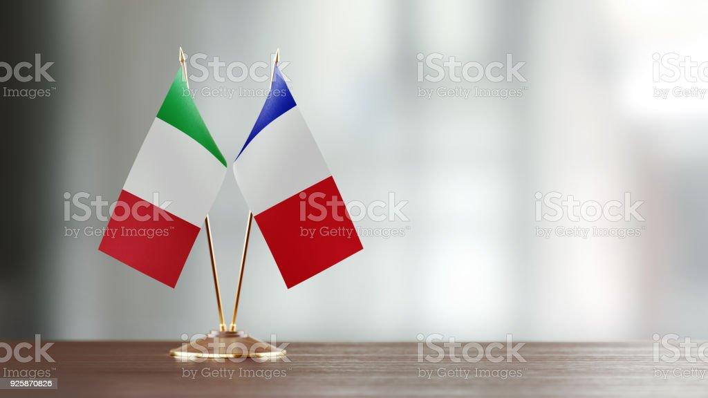 Par de la bandera italiana y francesa en un escritorio sobre fondo Defocused - foto de stock