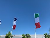 Italian and french flags blowing in the wind on blue sky