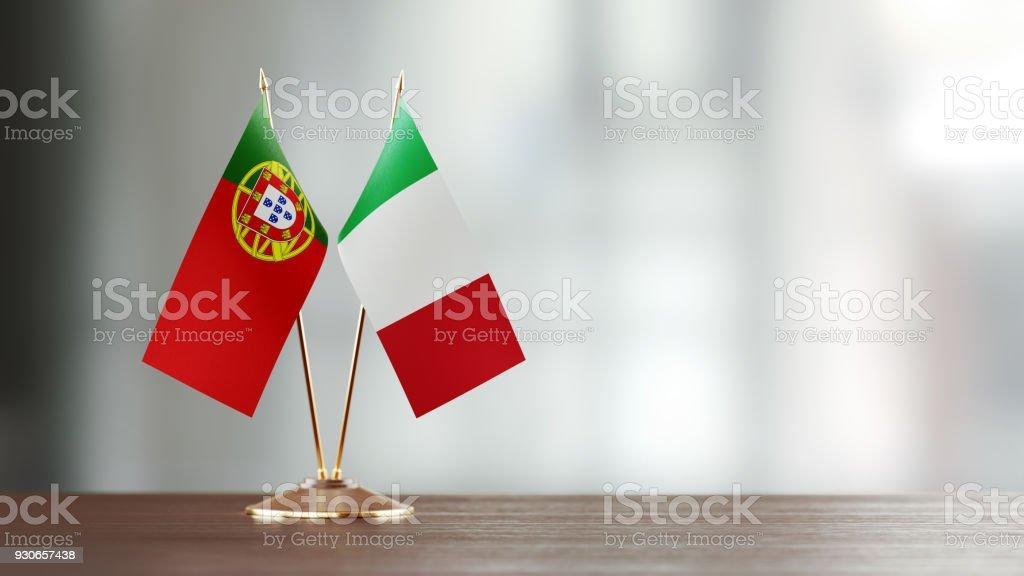 Le drapeau italien et portugais paire sur un bureau sur fond