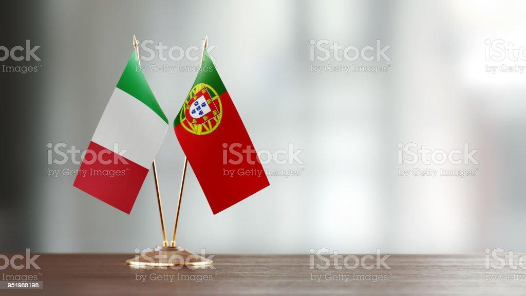 Par de bandeira italiana e portuguesa em uma mesa sobre fundo desfocado - foto de acervo