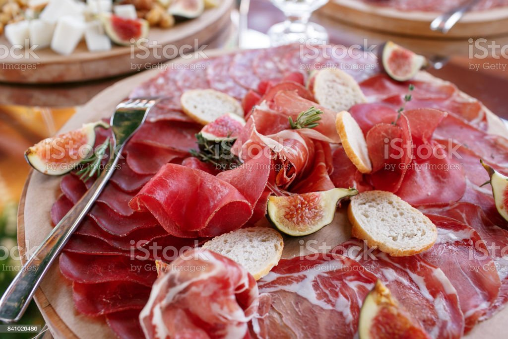 Italian antipasti and appetizers. board with slices prosciutto, salami, dried pork, salami ham with herbs. stock photo