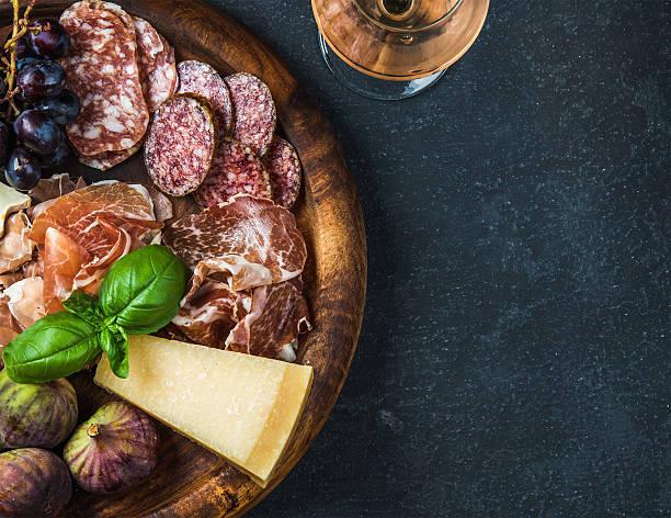 italian antipasti snack for wine on wooden tray, dark background - salami vorspeise stock-fotos und bilder
