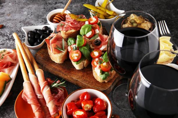 conjunto de petiscos entradas italianas vinho. variedade de queijo, mediterrâneas azeitonas, picles, presunto di parma, tomates, alcachofras e vinho em copos - comida italiana - fotografias e filmes do acervo