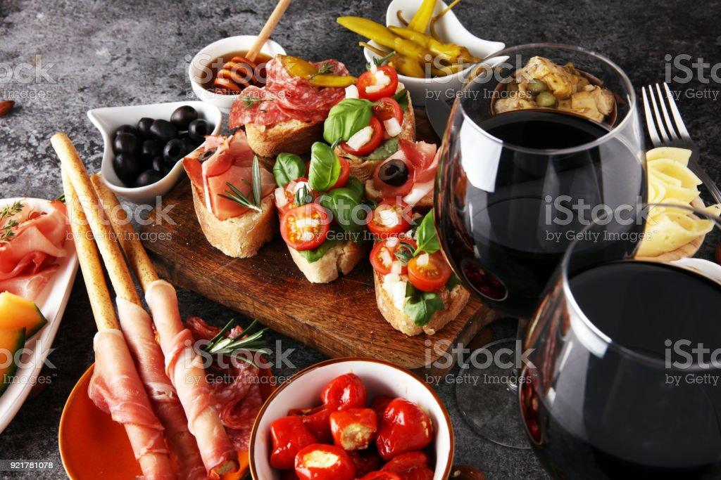 Italiaanse antipasti, wijn hapjes set. Verscheidenheid van kaas, mediterrane olijven, augurken, Prosciutto di Parma, tomaten, artisjokken en wijn in glazen foto