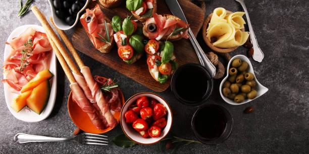 Italian antipasti wine snacks set. Cheese variety, Mediterranean olives, pickles, Prosciutto di Parma, tomatoes, artichokes and wine in glasses stock photo